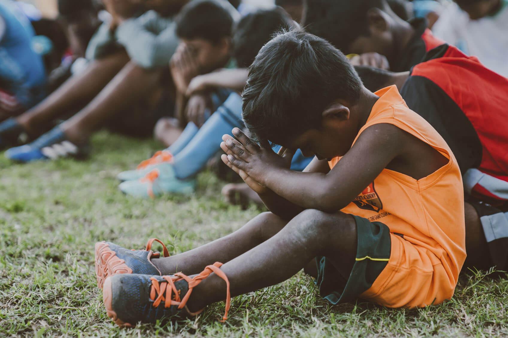 Young boy praying on football field
