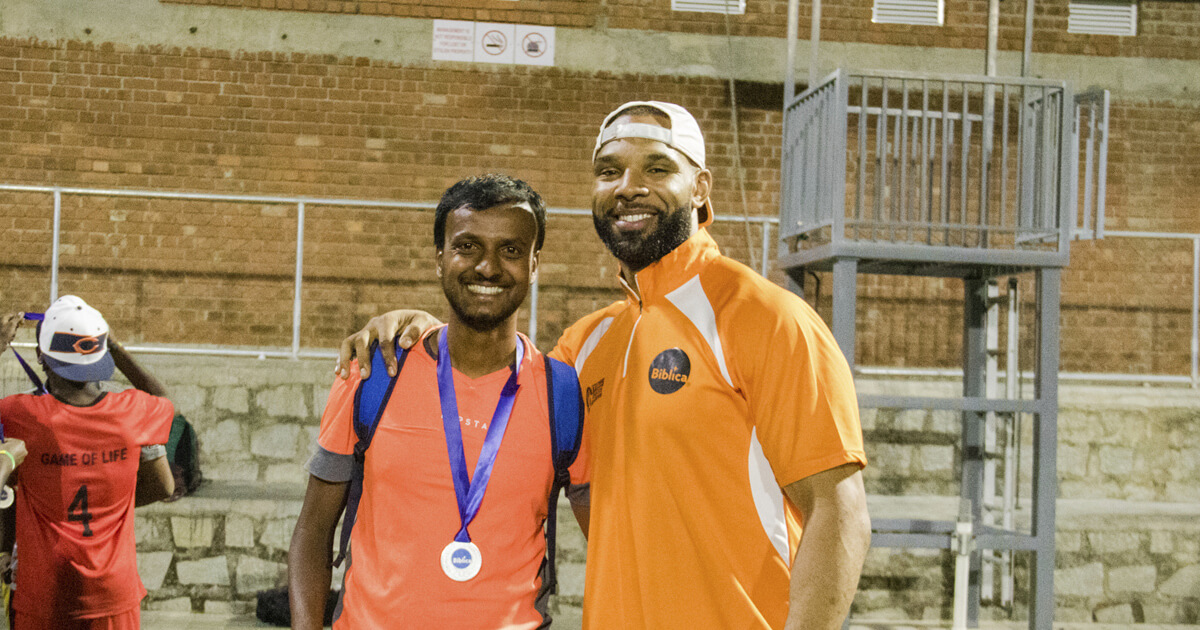 "Matt Forté standing with a teenage football player in India during a ""Game of Life"" event."