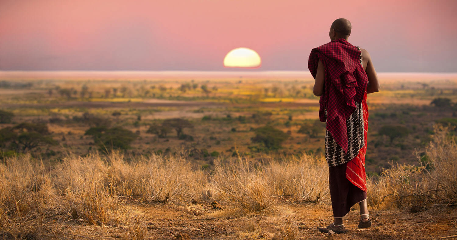 Man watching sunset on the plains of Africa