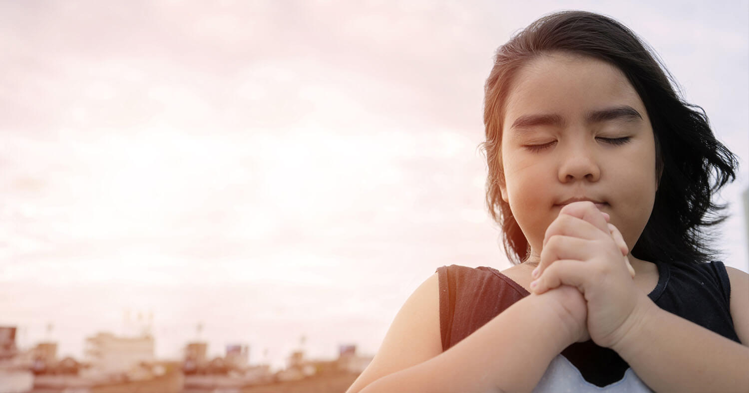 Young Hispanic girl praying with folded hands.